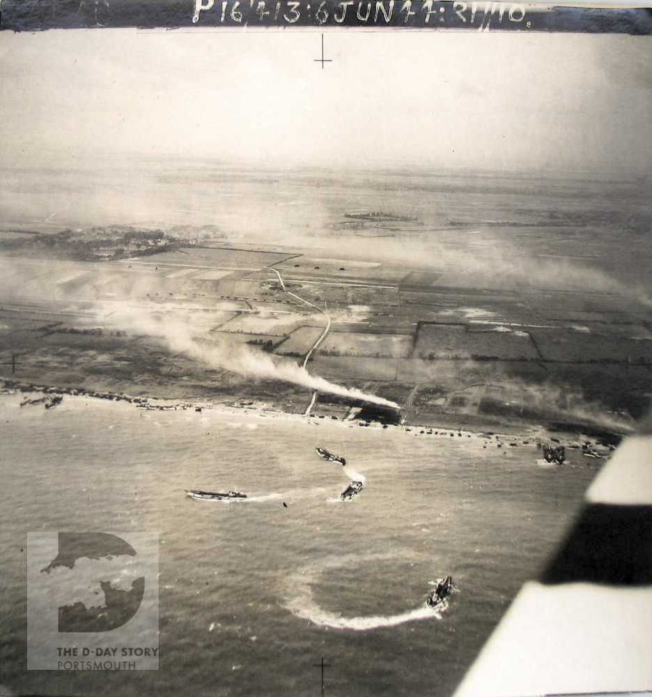 This aerial photograph of Gold Beach on D-Day. Landing craft can be seen just off the coast. The black and white stripes on the right are part of the wing of the aircraft.