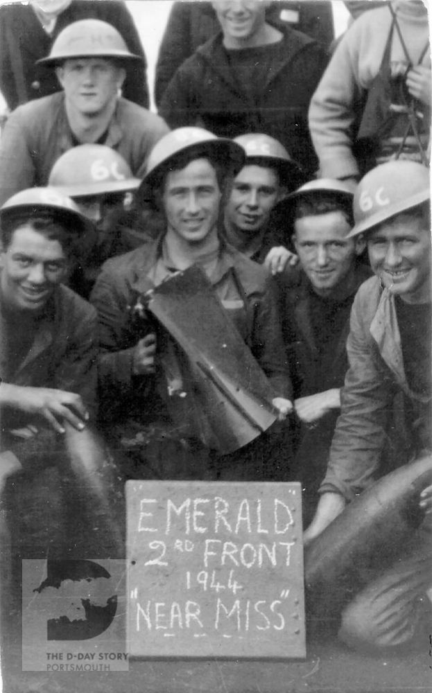 Crewmen from HMS Emerald pose with the tail fin of a German bomb that hit their ship on the night of D-Day. Fortunately the bomb bounced off into the sea without exploding, leaving behind this souvenir.