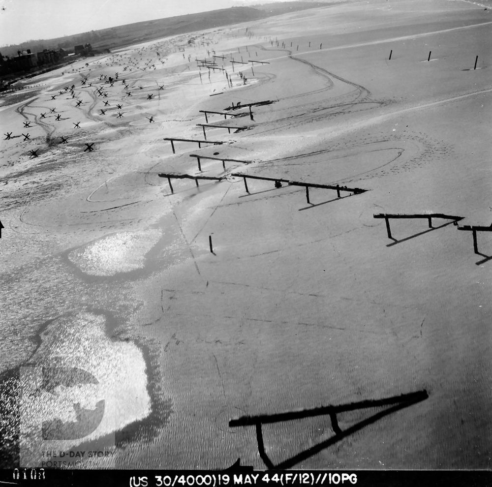 This photograph, taken before D-Day, shows lines of German obstacles on Gold Beach. The obstacles were designed to sink or capsize Allied landing craft.