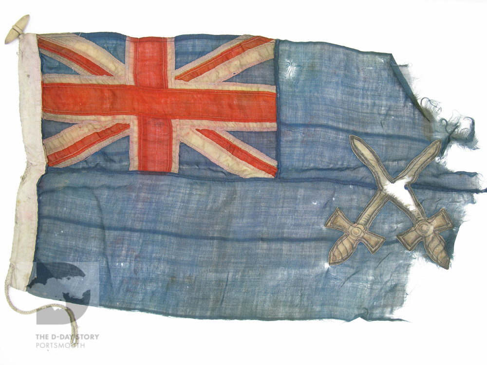 This blue ensign flag was flown by the yacht 'Swallow' at Juno Beach on D-Day. She was operated by the British Army and helped organise ships unloading supplies.