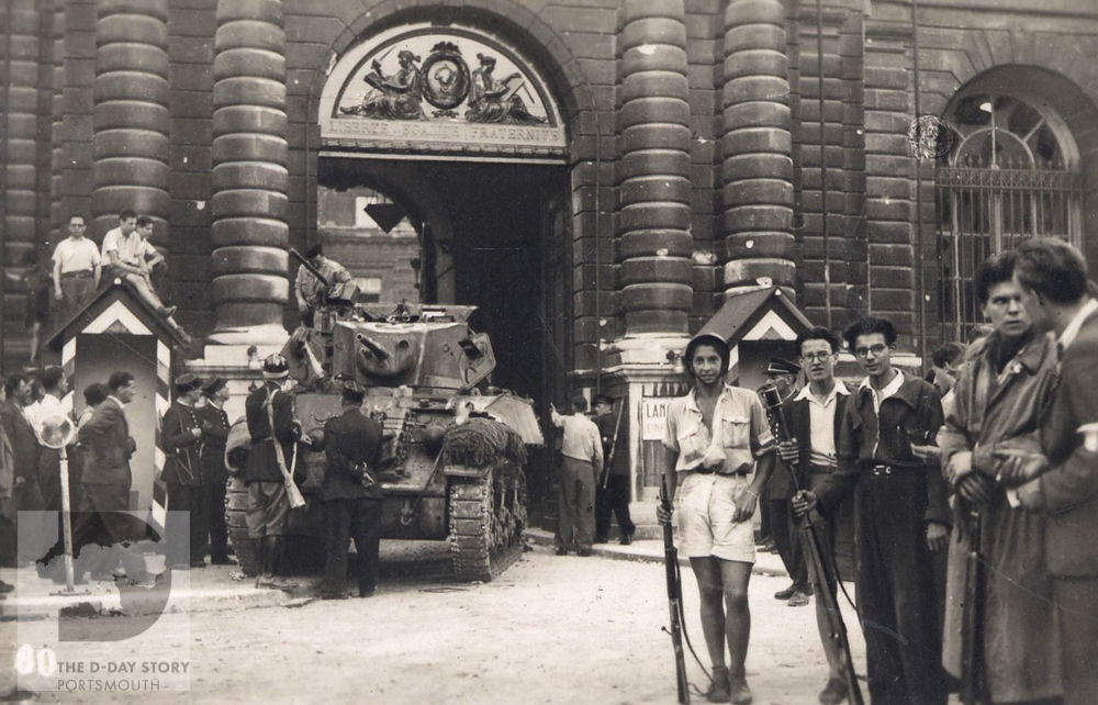 French troops and Resistance fighters guard a public building in Paris during the liberation of the city.