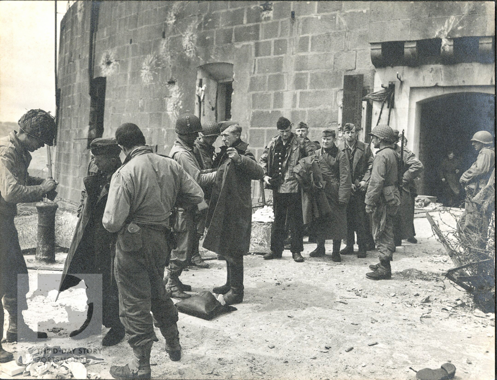 US troops search German soldiers who have just surrendered, in the former French arsenal at Cherbourg.