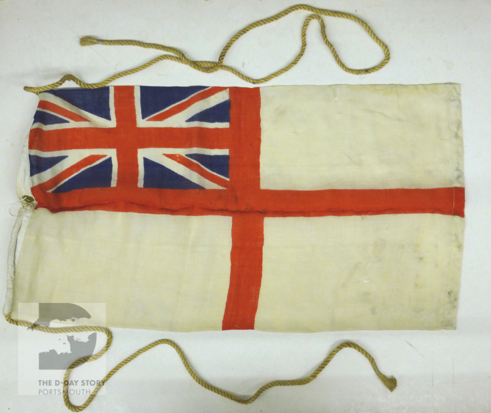 A white ensign flag that was flown on a landing barge that took supplies to Normandy. The barge was meant to arrive on D-Day, but had engine trouble and was a day late.
