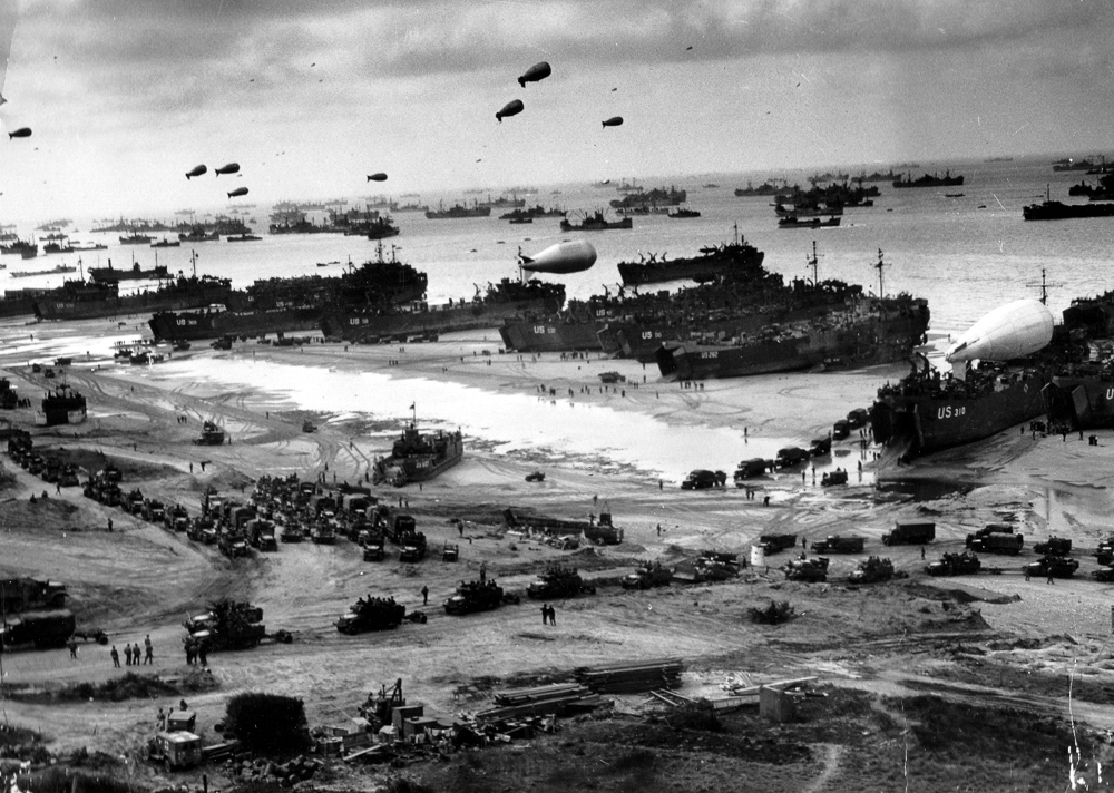 Allied ships unload troops and supplies at Omaha Beach several days after D-Day.