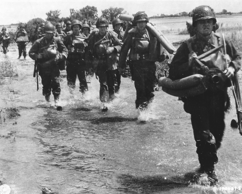 Soldiers of 4th US Infantry Division make their way inland from Utah Beach.
