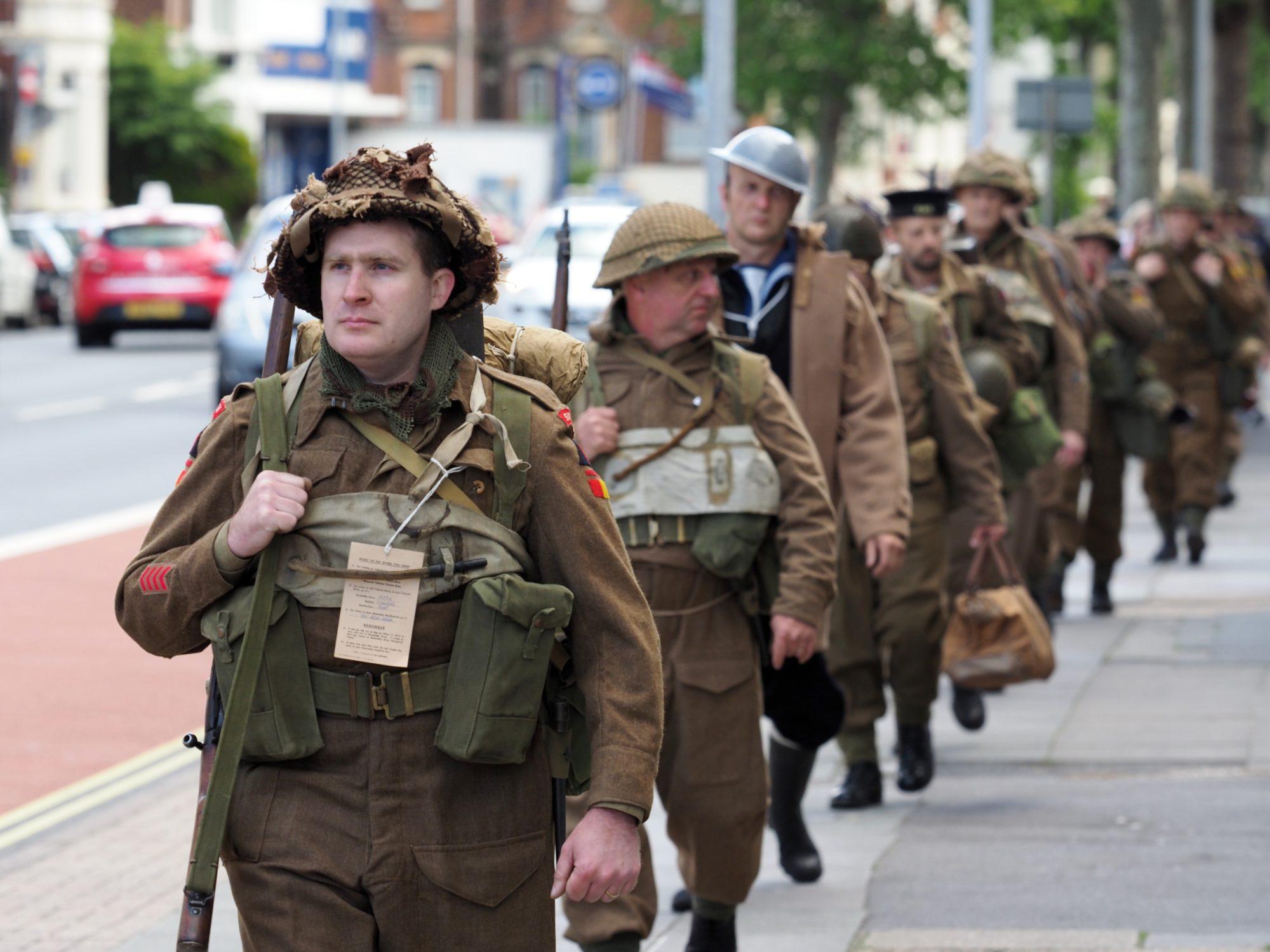 Re-enactors walking down the street for We Knew Something Was Happening