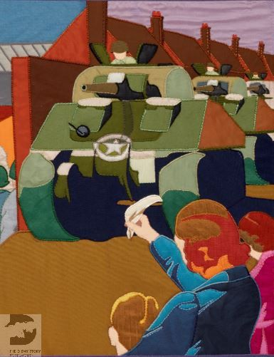 A section of the Overlord Embroidery. A woman and small child have their backs to the viewer. They are waving at a Sherman tank that is passing by.
