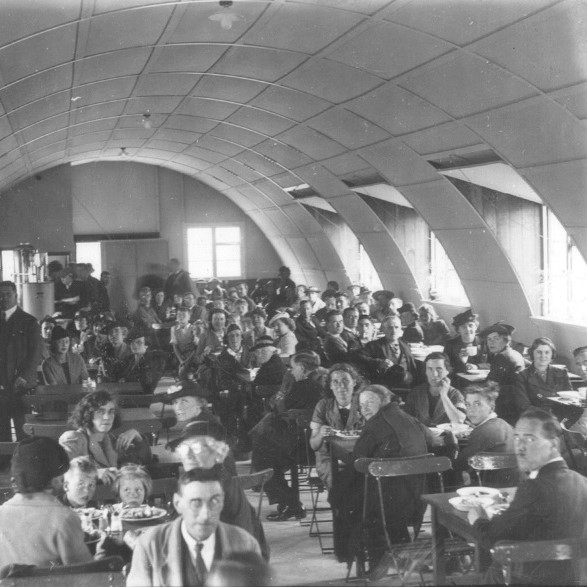 A black and white photograph of people eating out in a wartime British Restaurant. They are sat at tables in a canteen style restaurant. Some are looking at the camera.