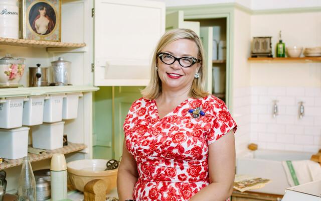 A photograph of Professor Deborah Sugg Ryan in a 1940s kitchen.