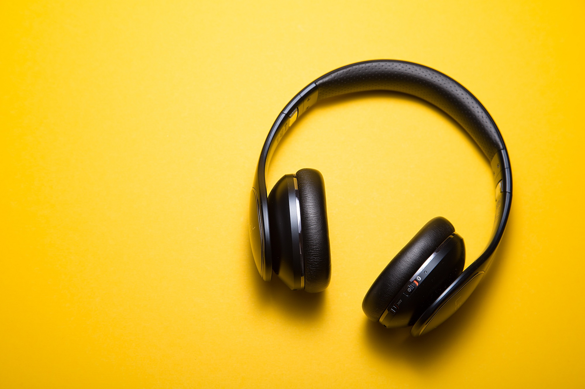 Stock images of black headphones on a yellow background