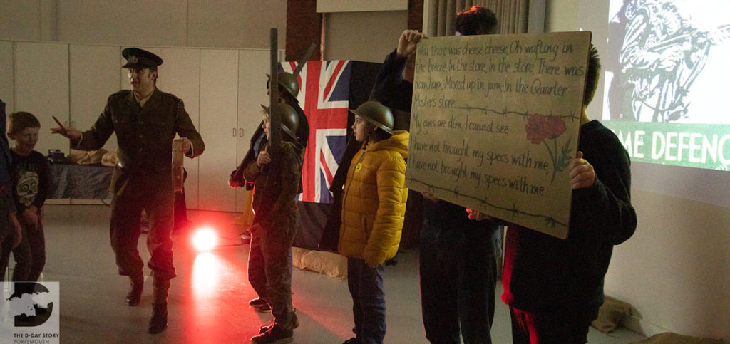 A photograph of an event at the D-Day Story. A man is moving towards the audience. Members of the audience stand on stage, they are dressed as soldiers and holding up the lyrics to a wartime song.