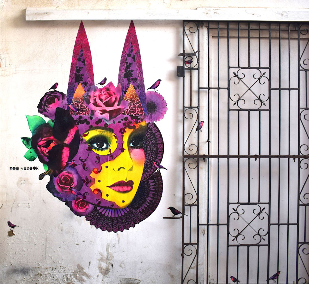 A photograph of a painted artwork on a wall. It is the face of a woman with yellow skin, her face surrounded by purple hair and flowers. There is an iron grated gate next to the artwork.